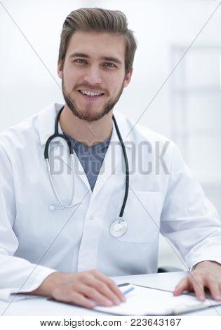 friendly doctor sitting behind a Desk