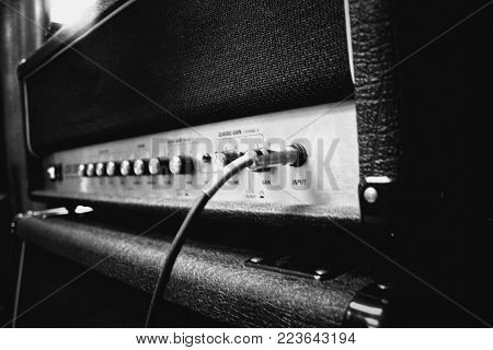 close up of a guitar amplifier on a stage - Black and White grainy instagram style filtered image