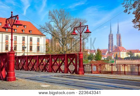 Wroclaw Poland. Red street lamps on Sand Bridge. View to cathedral of Saint John the Baptist on Tumski island.