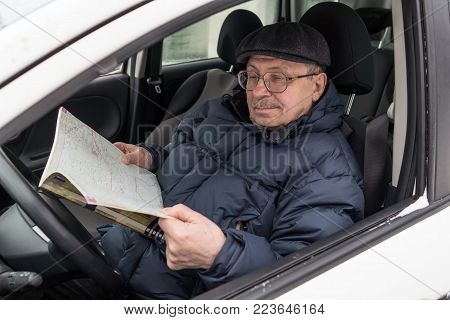 An elderly man is sitting at the wheel of a car. The pensioner reviews the road map and chooses a route for the trip. Active old age. Winter, day.