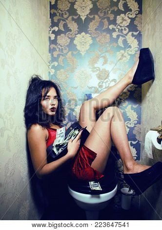 pretty young african mixed asian woman in luxury restroom with money, like prostitute, dirty cash concept close up