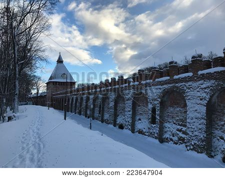 Fortress wall of Smolensk in the winter. Part of the fortress wall and tower in winter. Along the wall around the snow, a small well-worn footpath along the wall. Blue sky, the sun hid behind a cloud.