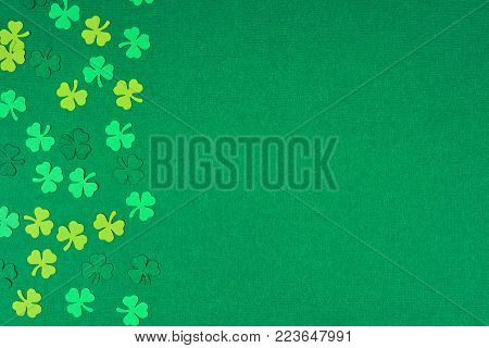 St Patricks Day side border of paper shamrocks over a green textured background