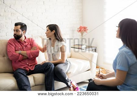 Beautiful young woman trying to make up quarrel in front of relationship counselor