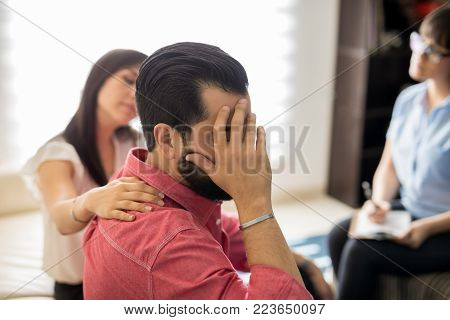Depressed man sitting with hand on head with wife trying to comfort him. Couple during psychotherapy session.