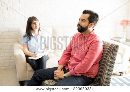 Handsome young man is sitting on chair during the psychotherapy session with female psychologist