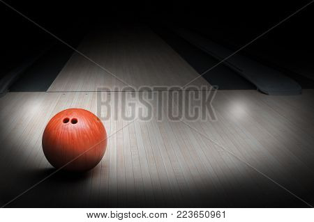 Bowling ball on hardwood bowling alley with special spot lighting effect. Focus on foreground ball with copy space.