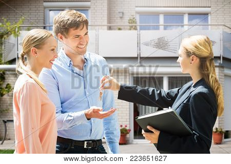 Female Real Estate Agent Giving House Key To Smiling Young Couple