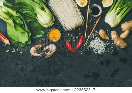 Asian cuisine ingredients over black background, top view, copy space. Flat-lay of vegetables, spices and sauces for cooking vietnamese, thai or chinese food. Clean eating, vegetarian diet concept