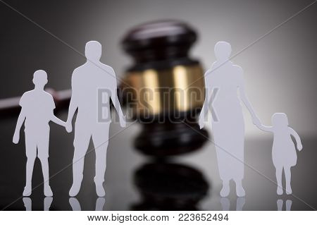 Separation Of Family Figure Cut Out In Front Of Gavel On Grey Background