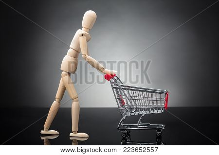 Side View Of A Wooden Dummy Pushing Shopping Cart On Grey Background