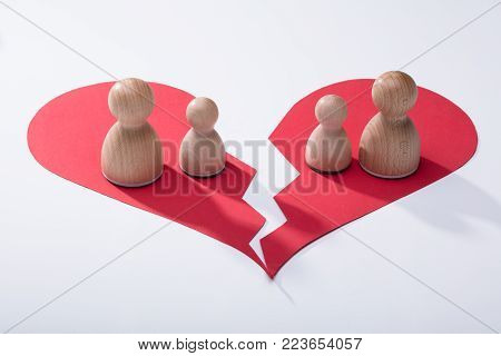 Wooden Pawns On Broken Red Heart Over White Background