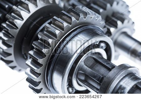 A close up detail shot of metal cogs, bearings, and gear shafts.