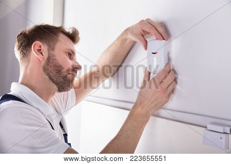 Close-up Of Young Male Electrician Installing Security System Door Sensor On Wall