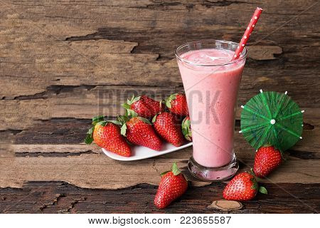 Strawberry yogurt smoothies, fruit juices and strawberry fruits. Drink on a healthy summer vacation on an old wood background.