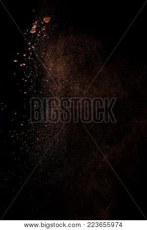 Cocoa powder explosion in motion. Chocolate dust on a black background. Action food photography.