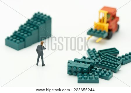 Miniature people businessmen standing with High-lifted forklift trucks are a great way to grow your business as a high-tech, high-growth joint venture. business concept with copy spaces for your