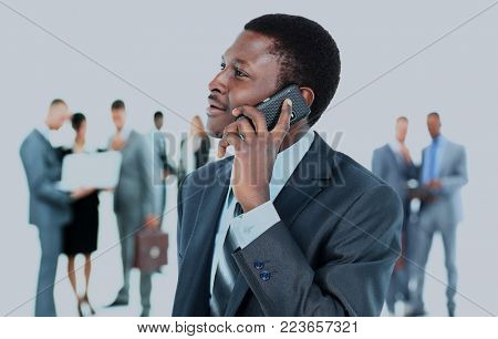 Smiling handsome business man using cell phone with colleagues in background.