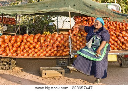 African woman street vendor with oranges and banana
