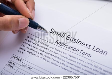 Close-up Of A Businessperson's Hand Filling Small Business Loan Application Form