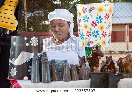Zezuru African woman street vendor with cow bells