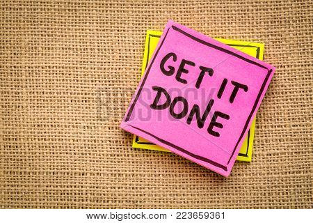 get it done advice or reminder handwriting on a sticky note against burlap canvas