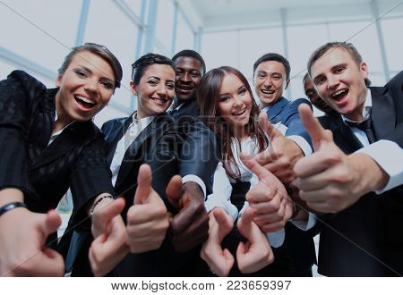 Happy multi-ethnic business team with thumbs up in the office.
