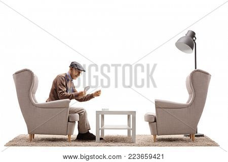 Senior seated in an armchair playing cards by himself isolated on white background