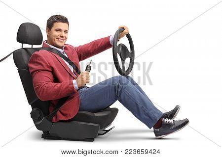Elegant guy seated in a car seat holding a steering wheel and a car key isolated on white background