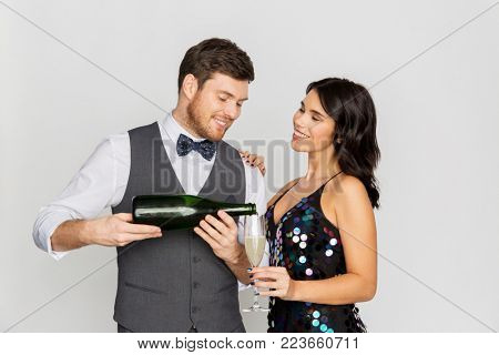 celebration and holidays concept - happy couple with bottle of non alcoholic champagne and wine glass at party