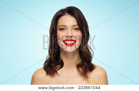 beauty, make up and people concept - happy smiling young woman with red lipstick over blue background