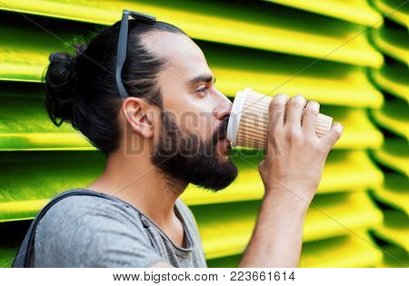 people, drinks and lifestyle concept - man drinking coffee from disposable paper cup on street over ribbed green wall background
