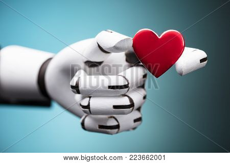 Close-up Of A Robot's Hand Holding Red Heart