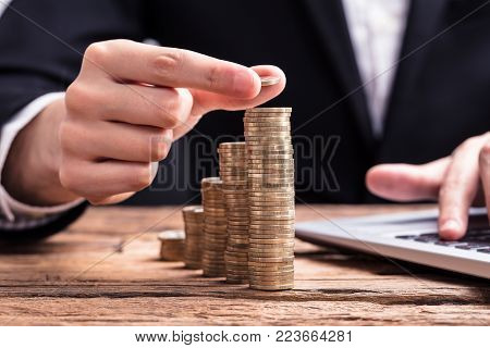 Close-up Of Businessperson's Hand Placing A Coin On Increasing Coin Stacks