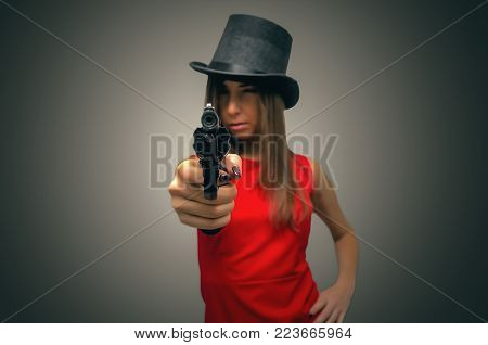 The spy. Special agent girl. Secret service. Dangerous sexy woman takes aim from the pistol in her hands isolated on white.