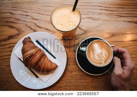 Top view. A man takes a cup of hot fragrant cappuccino. Near the table is a croissant and a glass with fresh orange juice. Morning breakfast.