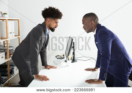Two Angry Young Businessmen Shouting At Each Other At Workplace