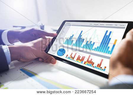 Close-up Of Two Businesspeople Working Together With Financial Graph On Digital Tablet