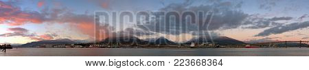 A panoramic winter view of North Vancouver from across the Burrard Inlet. The sun is setting and the snow and clouds of the North Shore mountains are illuminated in vibrant pink against a blue sky.