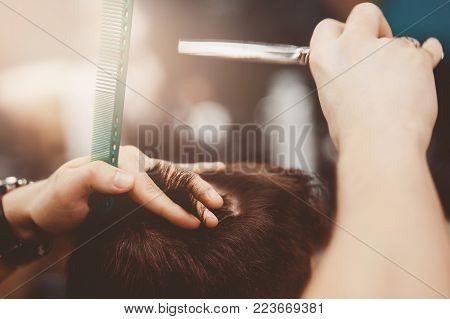 Barbershop. Man Barber in men's hairdresser does hair with scissors.
