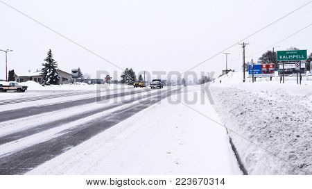 KALISPELL, MONTANA, USA - December 29, 2017: Vehicles driving past the Kalispell city limits sign on Highway 2 during a blizzard.