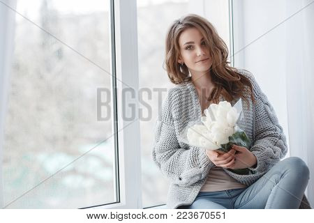 Winter Concept. Cute young girl in a gray knitted sweater. Beautiful woman is relaxing in a white bedroom. Beautiful women in winter clothes are waking up in the morning. Woman wearing a sweater in a white bedroom.