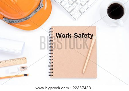 Work safety concept. Top viwe of modern workplace with safety helmet, office supplies, a cup of coffee and keyboard on white background.