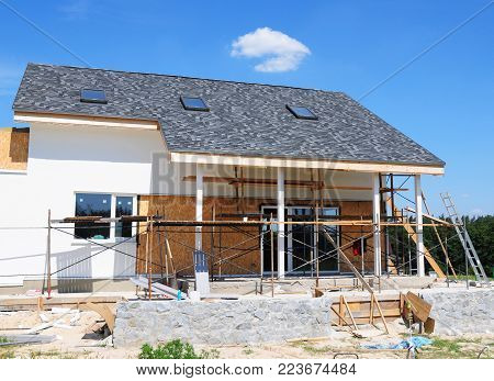 Unfinished house. Home Remodeling and Renovation. Painting house wall with stucco and plastering. Insulation House Wall and Renovation. Roofing construction with asphalt shingles.