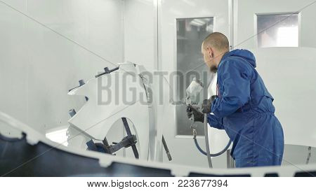 Auto painter spraying white paint on car spare fender in special booth. Painting vehicle parts at car service workshop