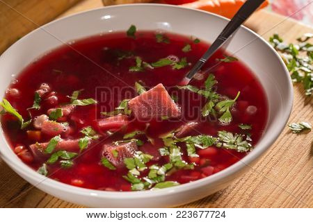 Traditional Romanian beet borscht in white bowl with spoon