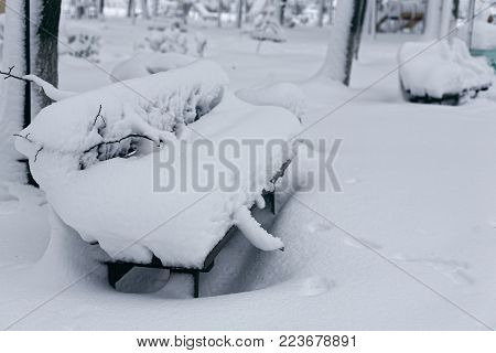 A photo of a bench in a winter park. An empty, lonely bench marked by a snowdrift.