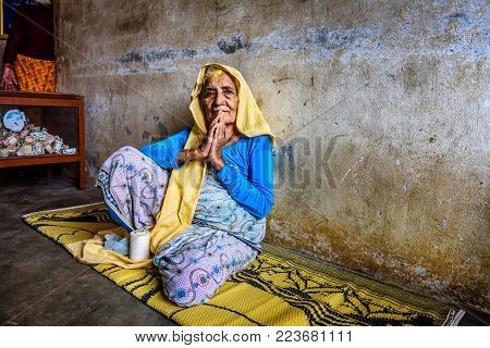 KATHMANDU, NEPAL - OCTOBER 23, 2015 : Very old woman welcomes visitors in a local retirement home