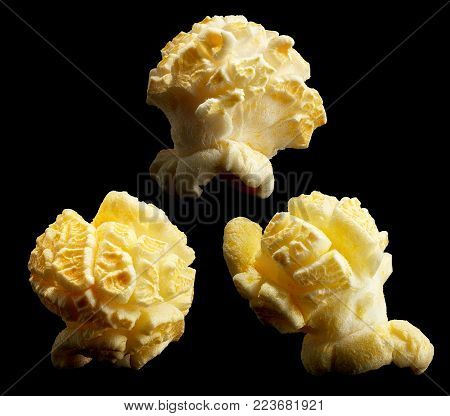Group of popped popcorn on a black background. Close-up or macro.