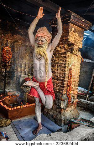 KATHMANDU, NEPAL - OCTOBER 21, 2015 : Shaiva sadhu with traditional long beard exercises in Pashupatinath Temple